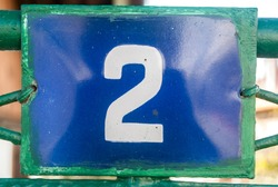 Weathered grunge square metal enameled plate of number of street address with number 2