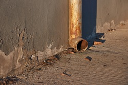 Weathered gutter channel pipe on a street in sunset light