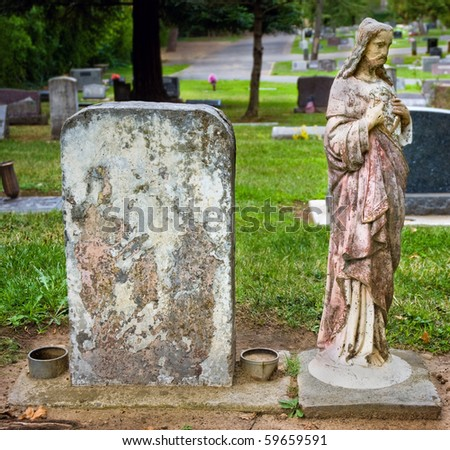 Weathered headstone with blank copyspace next to vintage statue of Jesus
