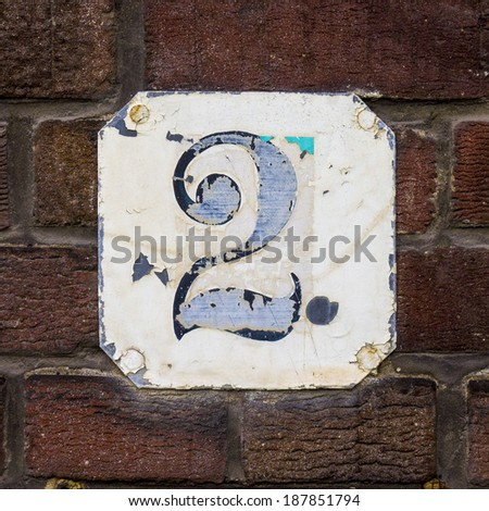 weathered house number two on a metal plate