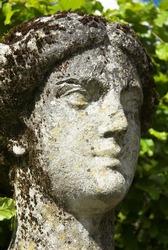 Weathered limestone figure head of garden statue.