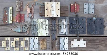 Weathered old hinges to be recycled and reused displayed on old rustic wood