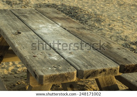 Weathered old picnic table sitting on the beach
