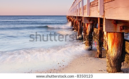 Weathered old pier in warm dawn sunlight.