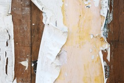 Weathered old vintage street posters on grungy wood background