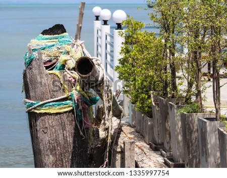 Weathered ornamentation on post at Bangsaray docks Thailand  #1335997754