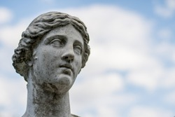 Weathered sculpture head of young Greek woman from mythology with blue sky and clouds in background