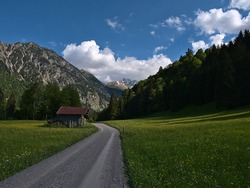 Weathered small wooden shed with red colored aluminium roof at gravel road surrounded by blooming meadows with wild flowers in a valley near Oberstdorf, Allgäu, Alps, Bavaria, Germany on spring day.