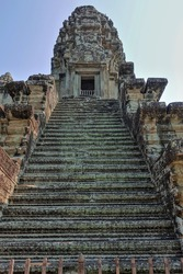 Weathered steps of a stone staircase lead to the top of the ancient temple. Tower with bas-reliefs and ornaments against the blue sky. The empty doorway is barred with bars. UNESCO. Angkor. Cambodia