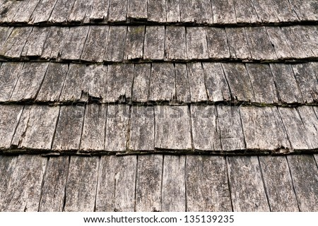 Weathered wooden shake shingles on a pitched roof show detail.