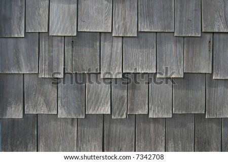 Weathered wooden shingles from the siding of a beach house