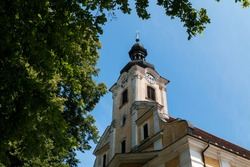 Weathered yellow facade with white details of the Saint Stephen (Svaty Stefan) church. Tower with clock. Tree with fresh leaves in the spring. Blue sky. Jablonica, Slovakia.