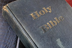 Weathering through times - front hardcover of a weathered, old and faded Holy Bible where many faithful Christians read the scripture for guidance, hope, inspiration and salvation.