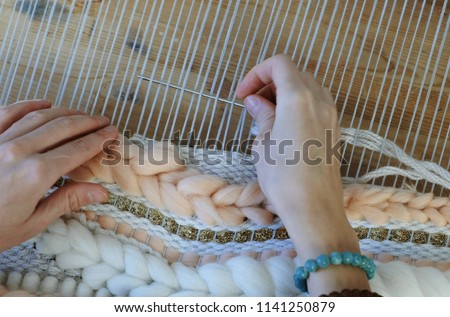 Weaving on a loom. Weaving on a loom. Closeup woman's hands running on a loom. Threading the needle through the strands of frame. Foto d'archivio ©