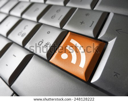 Web and Internet news concept with rss feed icon and symbol on a laptop computer key for blog and online business.
