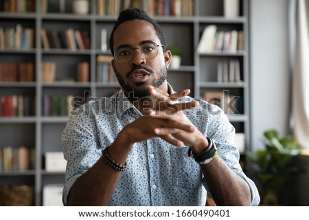 Web cam view serious concentrated young african ethnic businessman in eyeglasses holding video call negotiations with partners. Focused multiracial male job seeker talking to hr manager online.