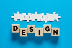 Web design or graphic design business or occupation concept. The word design on wooden cubes with a connected line of jigsaw puzzle.