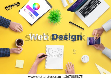 Web design team work on project concept. Yellow desk with web design text. Top view, flat lay.
