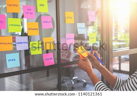Web designer brainstorming for a strategy plan. Colorful sticky notes with things to do on office board. User experience (UX) concept. #1140121361
