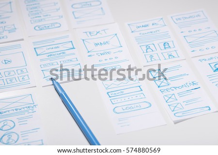 Web designer desk with sketches of screens for mobile application. Developing wireframe for mobile user experience