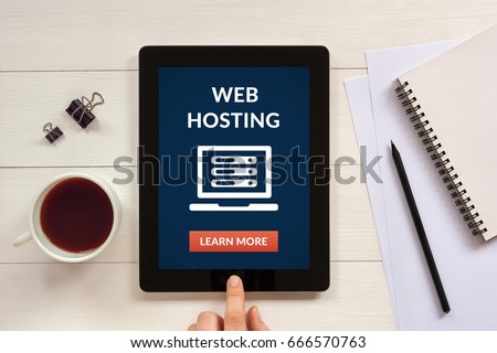 Web hosting concept on tablet screen with office objects on white wooden table. Flat lay