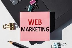 Web Marketing note is written on a paper sticker on a laptop keyboard