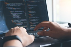 Web or application development, business and technology concept. Programmer, man software developer hands coding HTML, programming Javascript on laptop computer screen, back view close up