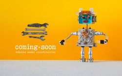 Web site under construction Coming Soon template page. Toy robot looks at a set of hand wrenches for maintenance repairs and service works. Orange wall and copy space on gray background