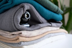 Webcam hidden in a stack of clothes for covert surveillance of the house. Surveillance and security systems. Smart House. Espionage. Hidden camera for watching