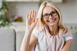 Webcam portrait of a happy mature caucasian blonde woman wearing eyeglasses, sitting on couch, looking directly at camera with friendly smile, waving hand, greeting gesture