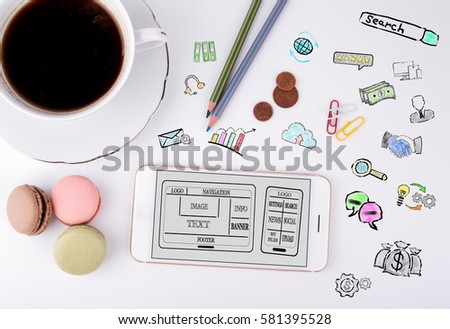 Website and mobile app development Concept. Mobile phone and coffee cup on a white office desk #581395528