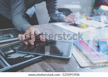 Website designer holding smart phone and working computer digital tablet on wood table,icon graph interface