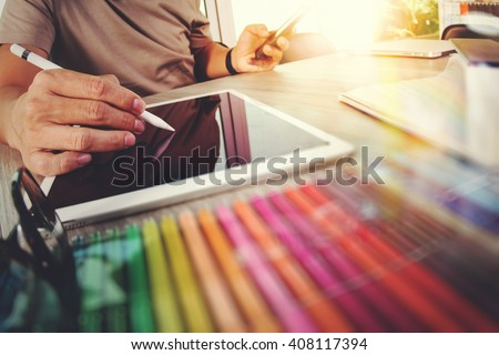Website designer working digital tablet and computer laptop with smart phone and graphics design diagram on wooden desk as concept #408117394