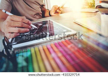 Website designer working digital tablet and computer laptop with smart phone and graphics design diagram on wooden desk as concept #410329714