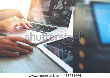 Website designer working with digital tablet and computer laptop and design diagram interface on wooden desk and compact server