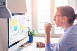 Website development UI/UX front end designer sketching wireframe layout design mockup for responsive web content in bright modern office