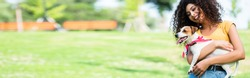 website header of laughing, curly woman holding jack russell terrier dog in park