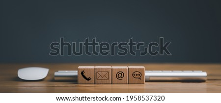 Website page contact us or e-mail marketing concept, Customer support hotline Contact us people connection. cube wood with the email, call phone, address, Chat message icons. on keyboard computer.
