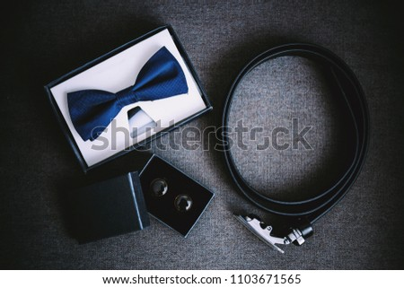 Wedding accessories. A blue bow tie, a black leather strap, black and gold cufflinks lie on a dark background.