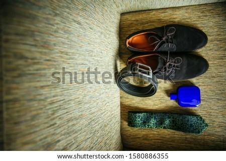 Wedding accessories for the groom, top view. Suede shoes, black leather belt, tie, eau de toilette.