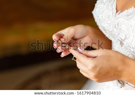 wedding accessories: the bride holds gold jewelry