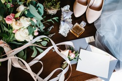 Wedding accessory bride. Stylish beige shoes, earrings, gold rings, flowers, garter, perfumes on table standing on wooden background. Letters from the bride and groom. flat lay. top view.
