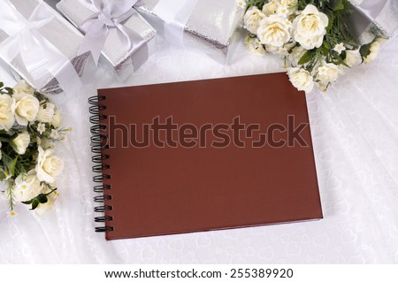 Wedding album or writing book laid on bridal lace with several silver wedding gifts and white rose bouquets.  Wedding list, record or photo album.  Space for copy.