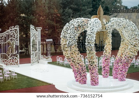 Wedding altar made of archs of pink, yellow and white flowers stands on the backyard