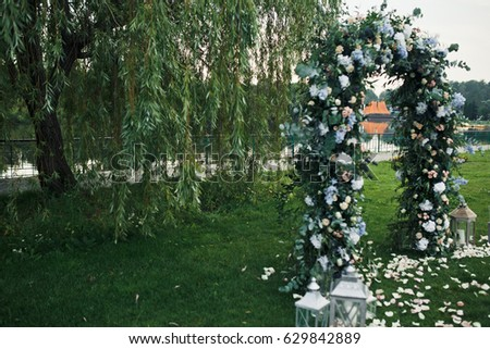 Wedding altar made of blue flowers stands on the green shore #629842889