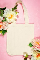Wedding and bridal party, Mother's Day or Spring theme tote bag SVG craft product flat lay mockup. Tote Bag with peony flowers on pink background.