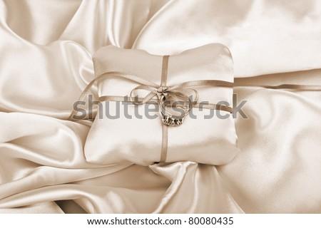 wedding and diamond engagement rings on silk presentation cushion