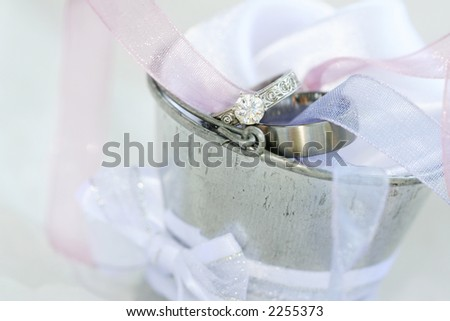 Wedding and engagement rings in a silver tin bucket.  Shallow D.O.F ? Rings in focus, foreground and background out of focus