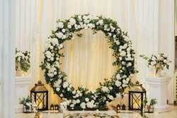 Wedding arch at the restaurant. Round flower arch. Trend in the wedding banquet room is a white  arch decorated with flowers and greens, in the background white cloth.