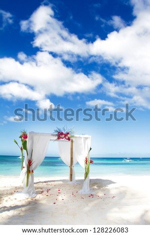 wedding arch decorated with flowers on beach